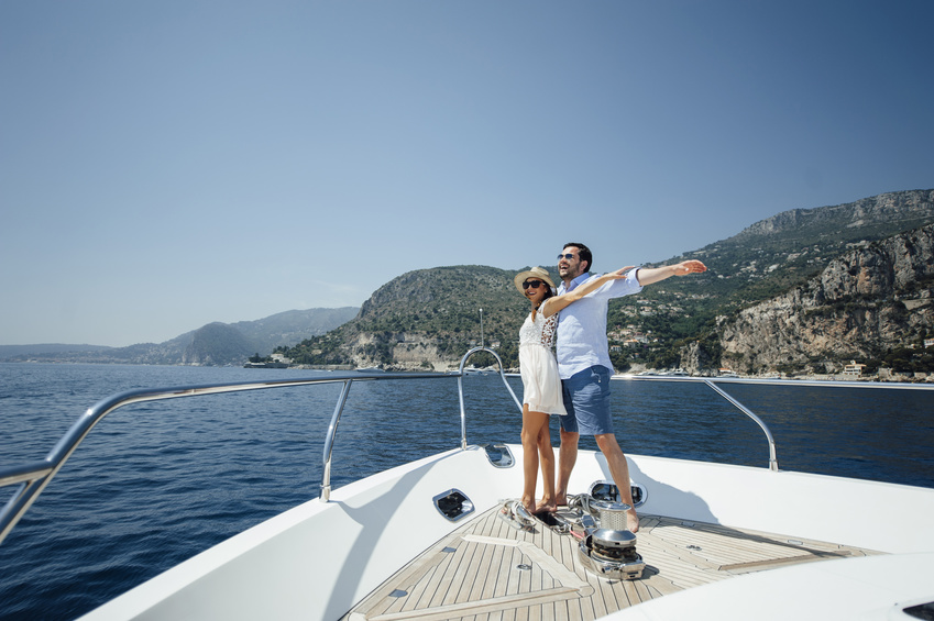Caucasian couple spreading arms out at the end of a yacht