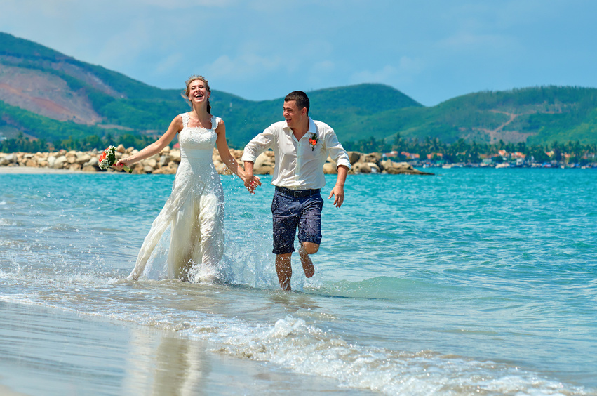 Bride and groom running along the beach